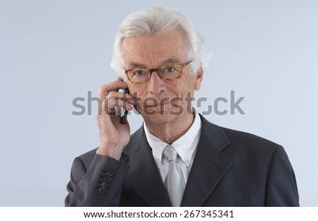 Senior  executive man giving explanations talking at phone mobile - stock photo
