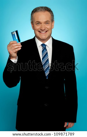 Senior executive showing credit card to camera - stock photo