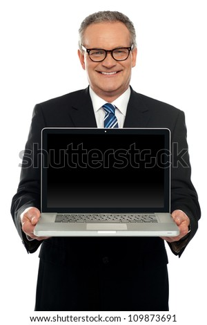 Senior executive standing with open laptop isolated against white background - stock photo