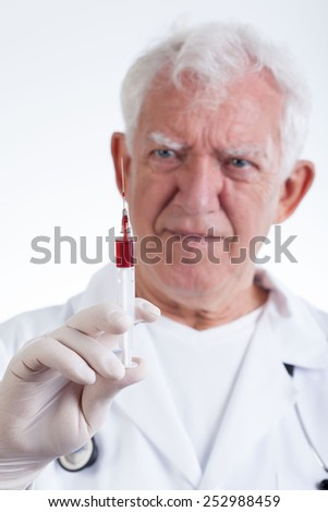 Senior expirienced physician with syringe  - stock photo