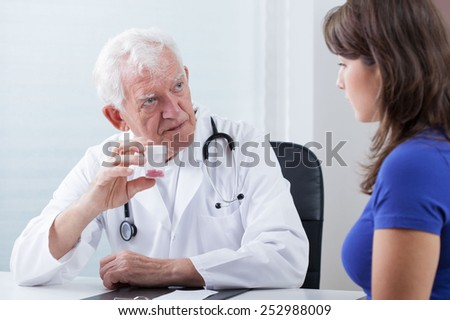 Senior family doctor recommending medicine to his patient - stock photo