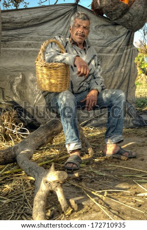 Senior farmer holding a basket and resting in nature - stock photo
