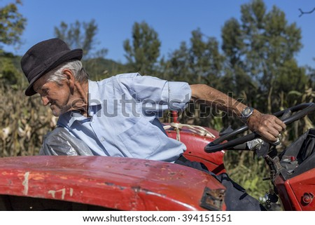 Senior farmer using an old tractor in the countryside - stock photo