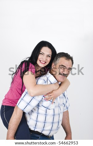 Senior father giving piggyback to her adult daughter and both laughing and having fun,copy space for text message - stock photo