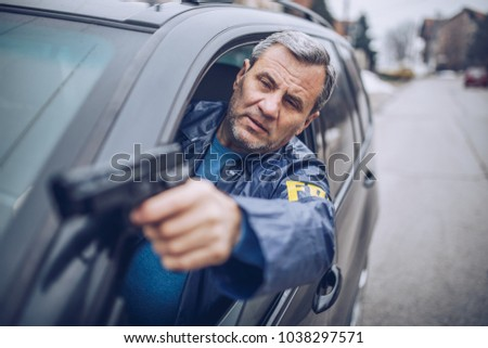 Senior FBI agent with a gun on a mission with a car