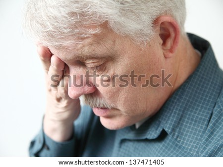 senior feeling very fatigued with hand over one eye - stock photo