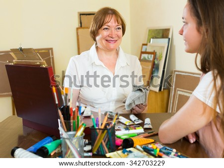 Senior female artist painting portrait of young girl at art studio with pencil and paints  - stock photo