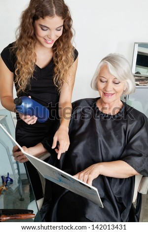 Senior female client and hairdresser choosing hair color at beauty salon
