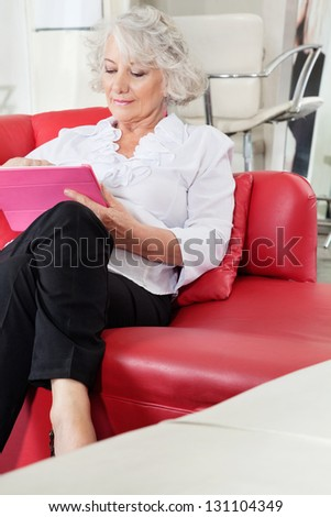 Senior female client using digital tablet at salon - stock photo