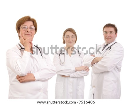 Senior female doctor and two young interns posing over white background - stock photo