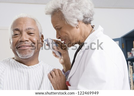 Senior female doctor checking patient's ear using otoscope