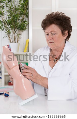 Senior female doctor demonstrate and explain the human body. - stock photo