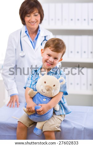 Senior female doctor examining happy child, smiling.