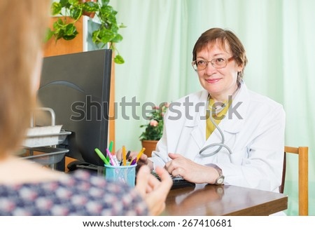 Senior female doctor inserting information about patient - stock photo