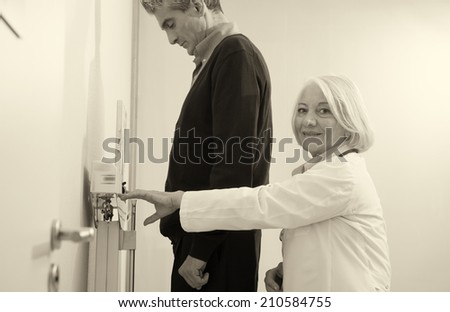 Senior female doctor weighing male patient. - stock photo