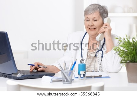 Senior female doctor, working at desk, using laptop computer. - stock photo