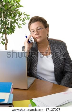 Senior female executive plowing through paperwork - stock photo