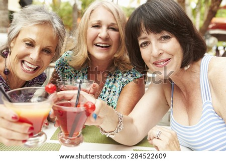 Senior Female Friends Enjoying Cocktails In Bar Together - stock photo