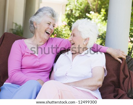 Senior female friends laughing together sitting on garden seat - stock photo