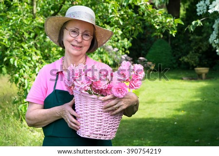 Senior female gardener in hat and apron smiling while holding basket of roses in yard during summer with copy space over grass area. - stock photo