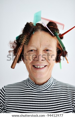 Senior female multitasking with many combs in hair - stock photo