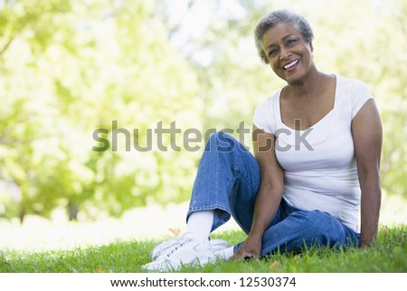 Senior female relaxing in park sitting on grass - stock photo