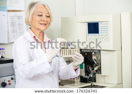 Senior female scientist analyzing blood sample in medical laboratory - stock photo