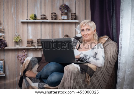 senior female sitting in cozy room and browsing internet with laptop; elder woman in chair and reading with portable computer;