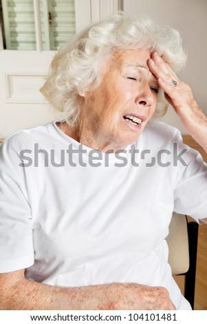 Senior female sitting on chair suffering from headache - stock photo