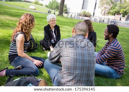 Senior female university professor teaching students outdoors - stock photo