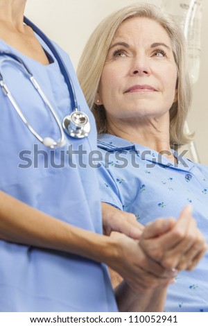 Senior female woman patient in a hospital bed having her pulse taken by a female nurse or doctor - stock photo