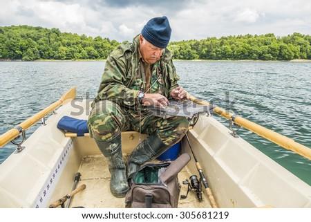 Senior fisherman preparing his gear on boat on Solina Lake in Poland - stock photo