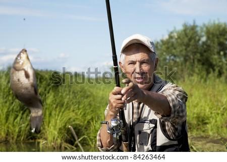 Senior fisherman with rod and fresh catch - stock photo