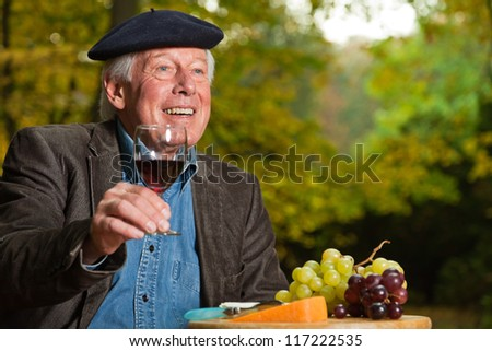 Senior french man enjoying red wine and cheese outdoors in autumn forest. - stock photo