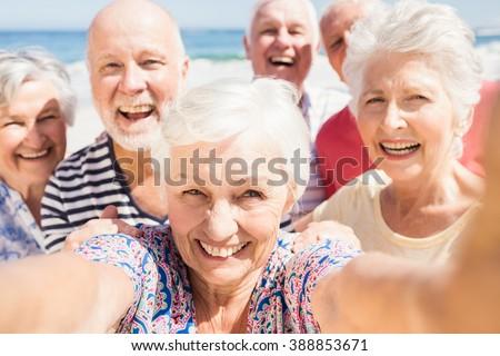Senior friends taking selfie on the beach - stock photo