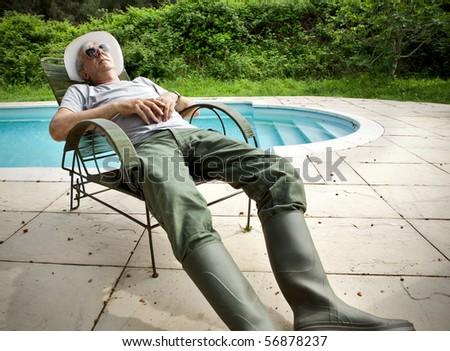 Senior gardener napping  poolside. - stock photo