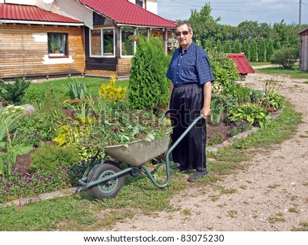 Senior gardener with wheelbarrow full of weeds