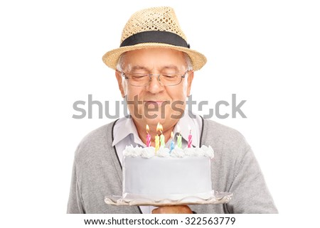 Senior gentleman blowing candles on a birthday cake isolated on white background - stock photo