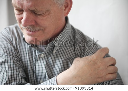 senior gentleman grimaces at the pain in his shoulder - stock photo