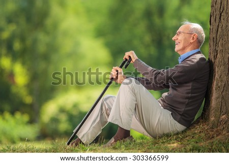 Senior gentleman holding a cane seated by a tree in a park on a beautiful summer day - stock photo