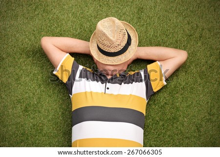 Senior gentleman lying in a field on green grass with the hat over his face - stock photo