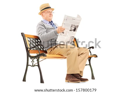 Senior gentleman reading newspaper and sitting on a wooden bench isolated on white background - stock photo