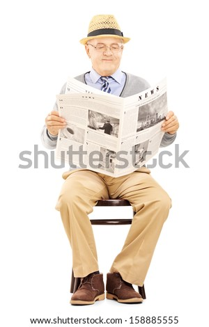 Senior gentleman reading newspaper and sitting on a wooden chair isolated on white background - stock photo