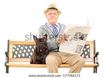 Senior gentleman sitting on a bench with his dog and reading a newspaper, isolated on white background. - stock photo