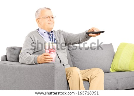 Senior gentleman sitting on a sofa and watching TV isolated on white background - stock photo