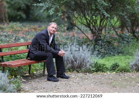 Senior gentleman sitting on wooden bench and relaxing in park, shot with a tilt and shift lens  - stock photo