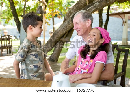 Senior gentleman spending wonderful time with grandchildren. Concept of love, affection and appreciation. - stock photo