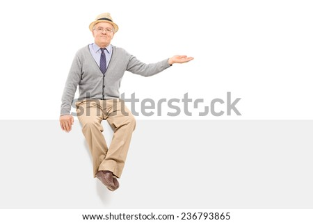 Senior gesturing with hand seated on a blank panel isolated on white background - stock photo