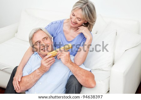 Senior giving his smiling woman a valentines day gift - stock photo