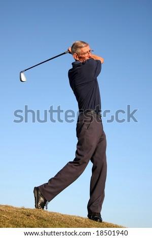Senior golfer playing a stroke on the fairway - stock photo